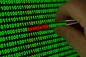 Hand reaching for the word Bankdaten, German for Banking information with tweezers in a binary code
